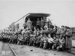 """სახალხო გვარდიის ჯავშანმატარებელთა რაზმის წევრები, ჯავშანმატარებელი N1 """"რესპუბლიკელის"""" ფონზე. ზედა რიგში მაუზერით ხელში და ბინოკლით რაზმის მეთაური, ვლადიმერ გოგუაძე. 1918-1921 წლები <br> Members of the division of armored train, on the background of armored train N1 """"Respublikeli"""". In the upper row is commander of the division Valodia Goguadze. 1918-1921"""