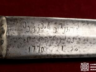 """მეფე ერეკლე II-ის ხმალი მიძღვნითი წარწერით """"მეფემან ერეკლემ თ. დადიან უძღვნა"""". <br> (თელავის ისტორიული მუზუეუმი) <br> როგორც ვარაუდობენ, ასპინძის ბრძოლის შემდეგ ეს ხმალი მეფე ერეკლემ თავის სიმამრს - კაცია დადიანს უძღვნა. ხმალი მემკვიდრეობით გადაეცემოდათ მის შთამომავლებს. ბოლოს მას სამეგრელოს უკანასკნელი მთავარი - დავით დადიანი ფლობდა. 1841 წლის გურიის აჯანყებისას დამარცხებული დავით დადიანის ხმალი გურულებთან აღმოჩნდა. 1941 წლიდან ხმალი ოზურგეთის მუზეუმში ინახებოდა, ხოლო 1983 წელს, გეორგიევსკის ტრაქტატის 200 წლისთავის აღნიშვნის დროს, თელავის ისტორიულ მუზეუმს გადაეცა. <br> გიორგი კაკაბაძის ფოტო. 2020 წელი."""