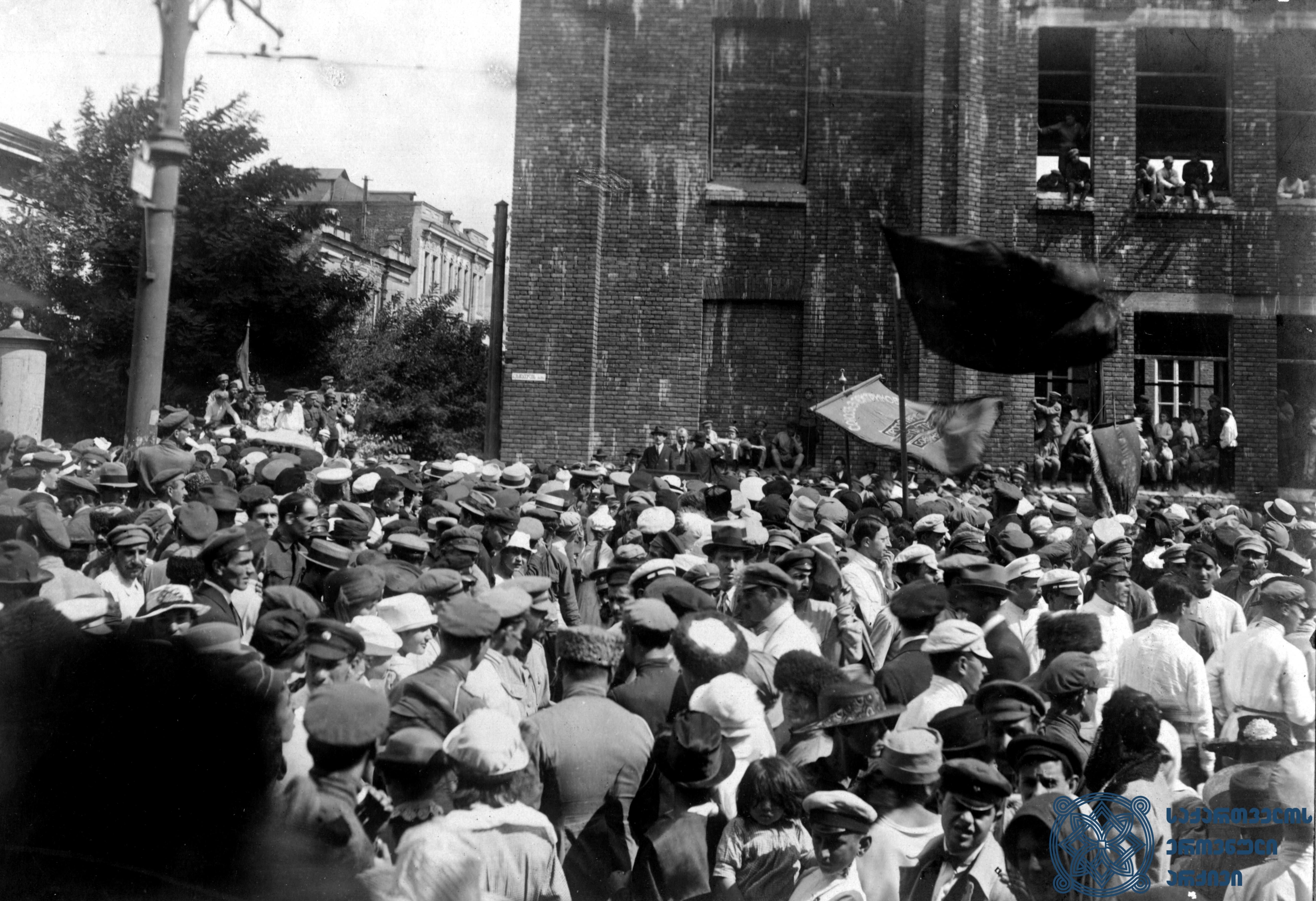 ბელგიელი სოციალისტის – კამილ ჰიუსმანსის – სიტყვით გამოსვლა თბილისში მეორე სოციალისტური ინტერნაციონალის დელეგაციის ვიზიტის პატივსაცემად გამართულ დემონსტრაციაზე. 1920 წლის სექტემბერი. <br> Belgian Socialist Camille Huysmans is giving a speech at a demonstration, held in Tbilisi, dedicated to the visit of the delegation of the Second Socialist International. September 1920.