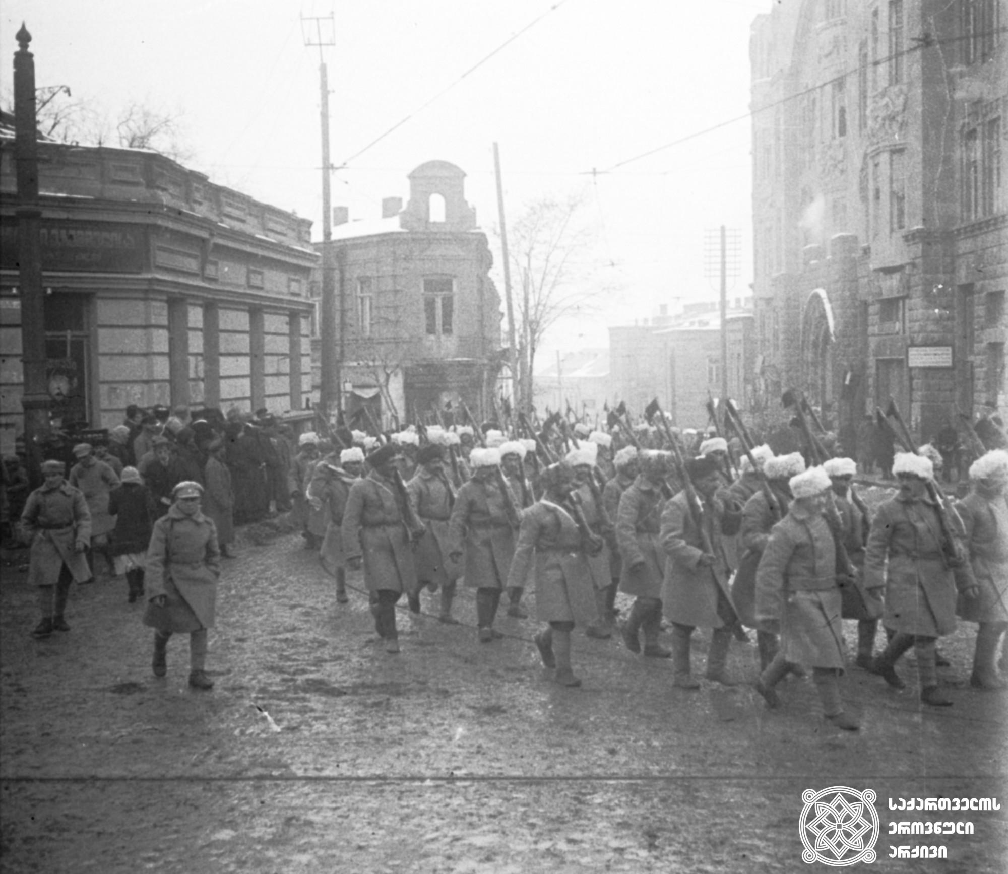 საქართველოს დე იურედ აღიარების საზეიმო აღლუმში მონაწილე ჯარისკაცები, რომელთაც ერთი კვირის შემდეგ რუსეთთან ომში ჩართვა მოუწიათ.  <br> თბილისი, 1921 წლის 6 თებერვალი.  <br> Soldiers taking part in a parade recognizing Georgia de jure, who had to join the war with Russia a week later.  <br> Tbilisi, February 6, 1921.