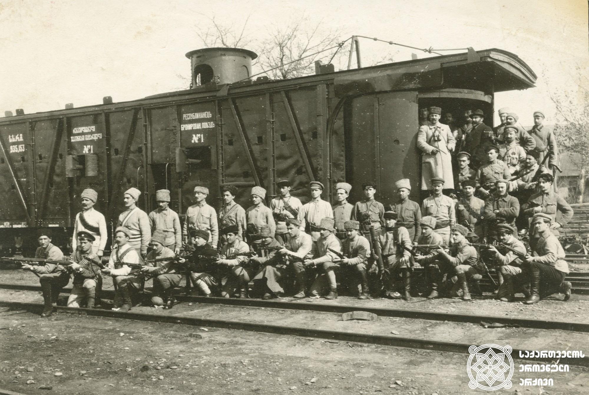 """სახალხო გვარდიის ჯავშანმატარებელთა რაზმის წევრები ჯავშანმატარებელი N1 """"რესპუბლიკელის""""ფონზე. <br> ფოტოზე ზედა რიგში მაუზერით ხელში და ბინოკლით რაზმის მეთაური ვლადიმერ გოგუაძე.  <br> 1918-1921 წლები. <br> Members of the division of armored train, on the background of armored train N1 """"Respublikeli"""".  <br> In the upper row is commander of the division Valodia Goguadze.  <br> 1918-1921."""