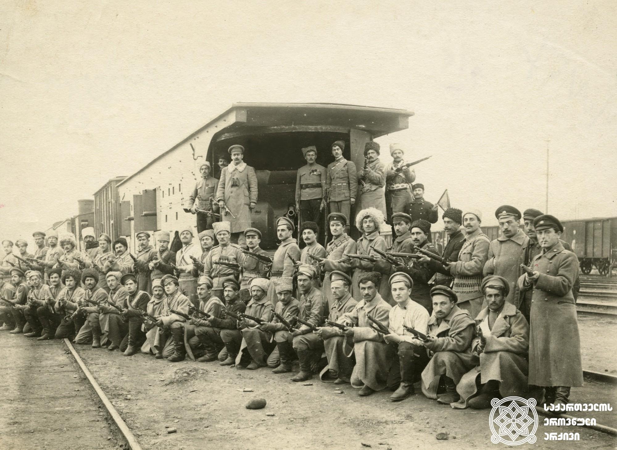 """ქართული არმიის ჯავშანმატარებელი.  <br> ჯავშანმატარებელთა რაზმში ირიცხებოდა ოთხი ჯავშანმატარებელი: """"რესპუბლიკელი"""", """"მუშა"""", """"სიკვდილიან გამარჯვება"""" და """"თავისუფლების სიმაგრე"""". შტატის მიხედვით, თითოეული ჯავშანმატარებელი აღჭურვილი იყო 1904 წლის მოდელის 2 სამთო ქვემეხითა და 12 ტყვიამფრქვევით, თუმცა, როგორც საარქივო დოკუმენტებიდან ჩანს, ქართველებმა მატარებლების საბრძოლო შესაძლებლობები გაზარდეს და არტილერიის რაოდენობა 3-4 ქვემეხამდე აიყვანეს, ხოლო ტყვიამფრქვევების რაოდენობა - 14-25-მდე.  <br> 1918-1921 წლები. <br>  Armored train of the Georgian Army. <br> Following four armored trains were counted in the division of the armored trains: """"Respublikeli"""" (Republican), """"Musha"""" (Worker), """"Sikvdili and Gamarjveba"""" (Death or Victory) and """"Tavisuflebis Simagre"""" (Independence Fortress). According to the staff each of the armored trains were equipped with two mining cannons of the model of 1904 and 12 machine-guns. Though according to the archival documents, Georgians increased the fighting opportunities of the trains and the artillery number was increased to 3-4 canons and 14-25 machine-guns. <br> 1918-1921."""