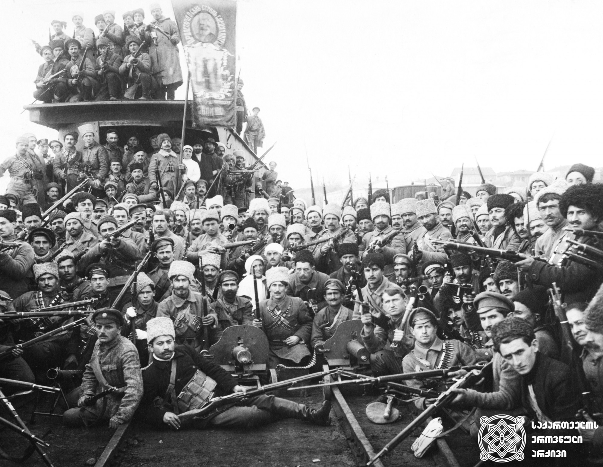 ქართველი გვარდიელები ჯავშნამატარებლით ქუთაისის რკინიგზის სადგურზე. <br> 1918 წლის თებერვალი. <br> Georgian Guardsmen on armored train at Kutaisi Railway Station. <br> February 1918.