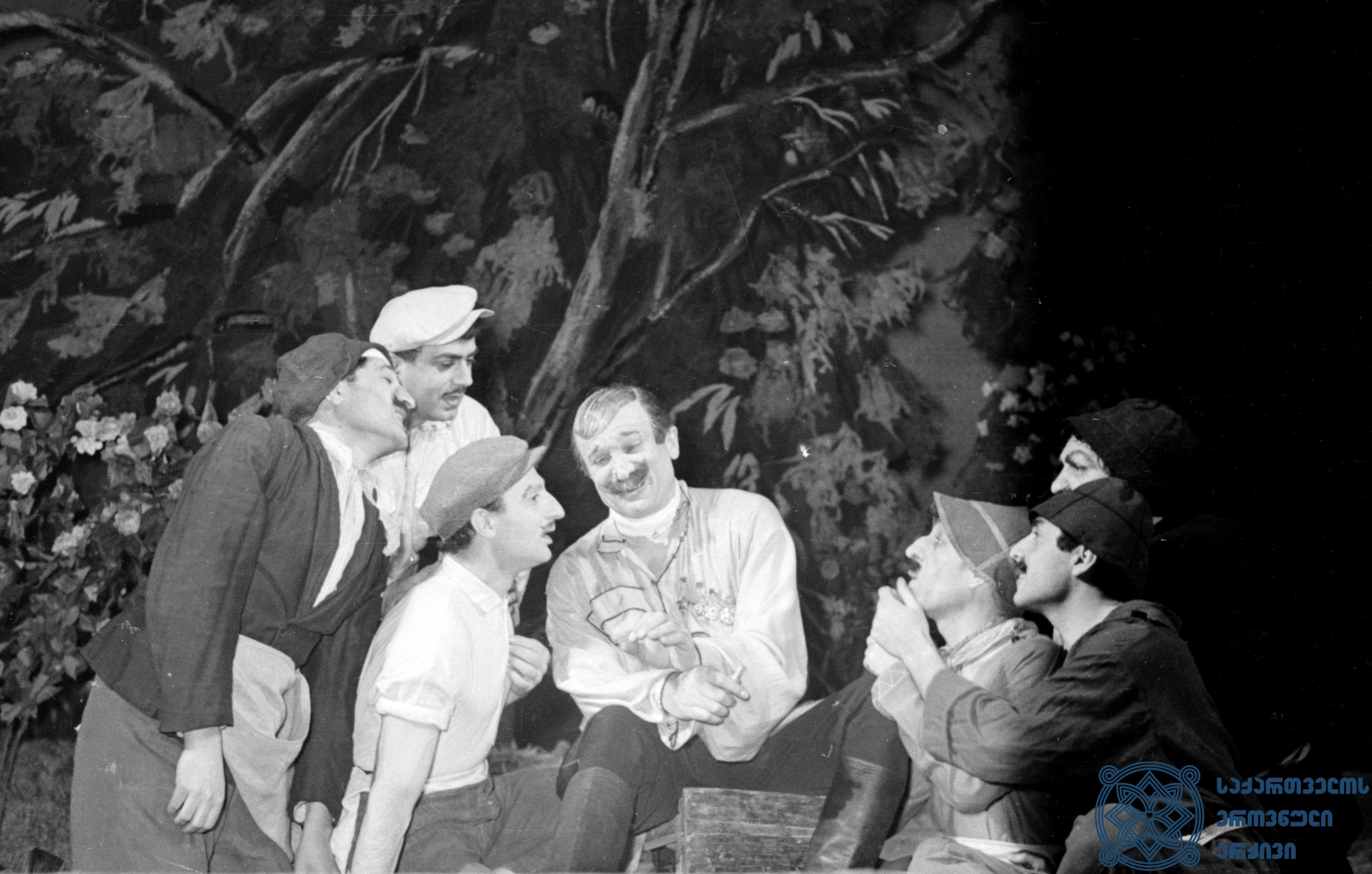 """მარჯანიშვილის სახელობის აკადემიური თეატრის სპექტაკლი """"კოლმეურნის ქორწინება"""". ბრიგადირები – თ. მაისურაძე, კ. მჟავანაძე, კ.თოლორაია, გ. დემეტრაშვილი, ბარამიძე; ხარიტონი (ცენტრში) – გიორგი შავგულიძე. <br> შალვა ღამბაშიძის დადგმა. 1959 წელი.<br> The Marjanishvili Academic Theater performance """"Marriage of Kolmeurne"""". Brigade leaders - T. Maisuradze, K. Mzhavanadze, K. Mzhavanadze, K. Toloraia, G. Demetrashvili, Baramidze; Giorgi Shavgulidze (in the center) as Khariton.<br> Shalva Gambashidze's staging. 1959."""