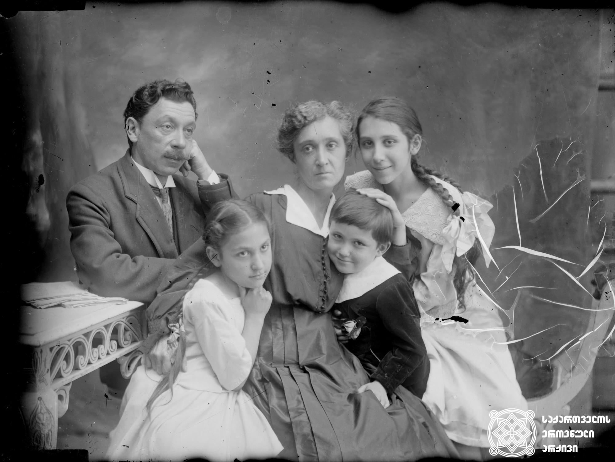 მსახიობი ნუცა ჩხეიძე მეუღლესთან, მიხეილ ქორელთან და შვილებთან ერთად. <br> მინის ნეგატივი 12X16. <br> Actress Nutsa Chkheidze with her husband, Mikheil Koreli and children. <br> Glass negative 12X16. <br>