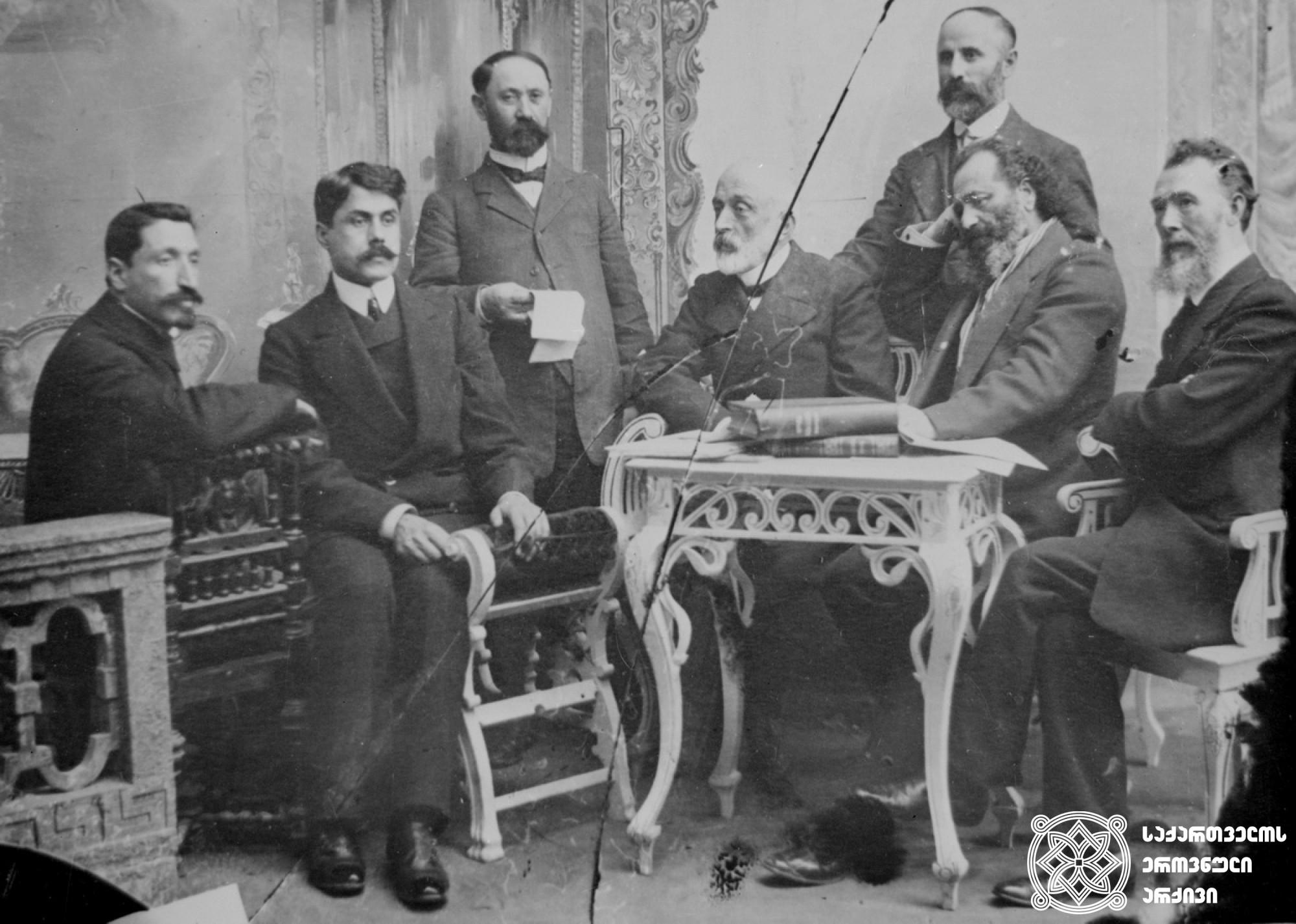 ქართველ მწერალთა და პოეტთა ჯგუფი. მარცხნიდან: ვარლამ რუხაძე, ჯაჯუ ჯორჯიკია, შიო მღვიმელი, იონა მეუნარგია, ია ეკალაძე, იასონ ნიკოლაიშვილი. მარჯვნივ დგას ისიდორე კვიცარიძე. [1910] <br> ფირის ნეგატივი 6X6. <br> Group of Georgian writers and poets. From left: Varlam Rukhadze, Jaju Jorjikia, Shio Mghvimeli, Iona Meunargia, Ia Ekaladze, Iason Nikolaishvili. Isidore Kvitsaridze stands on the right. [1910] <br> The negative of the tape is 6X6. <br>