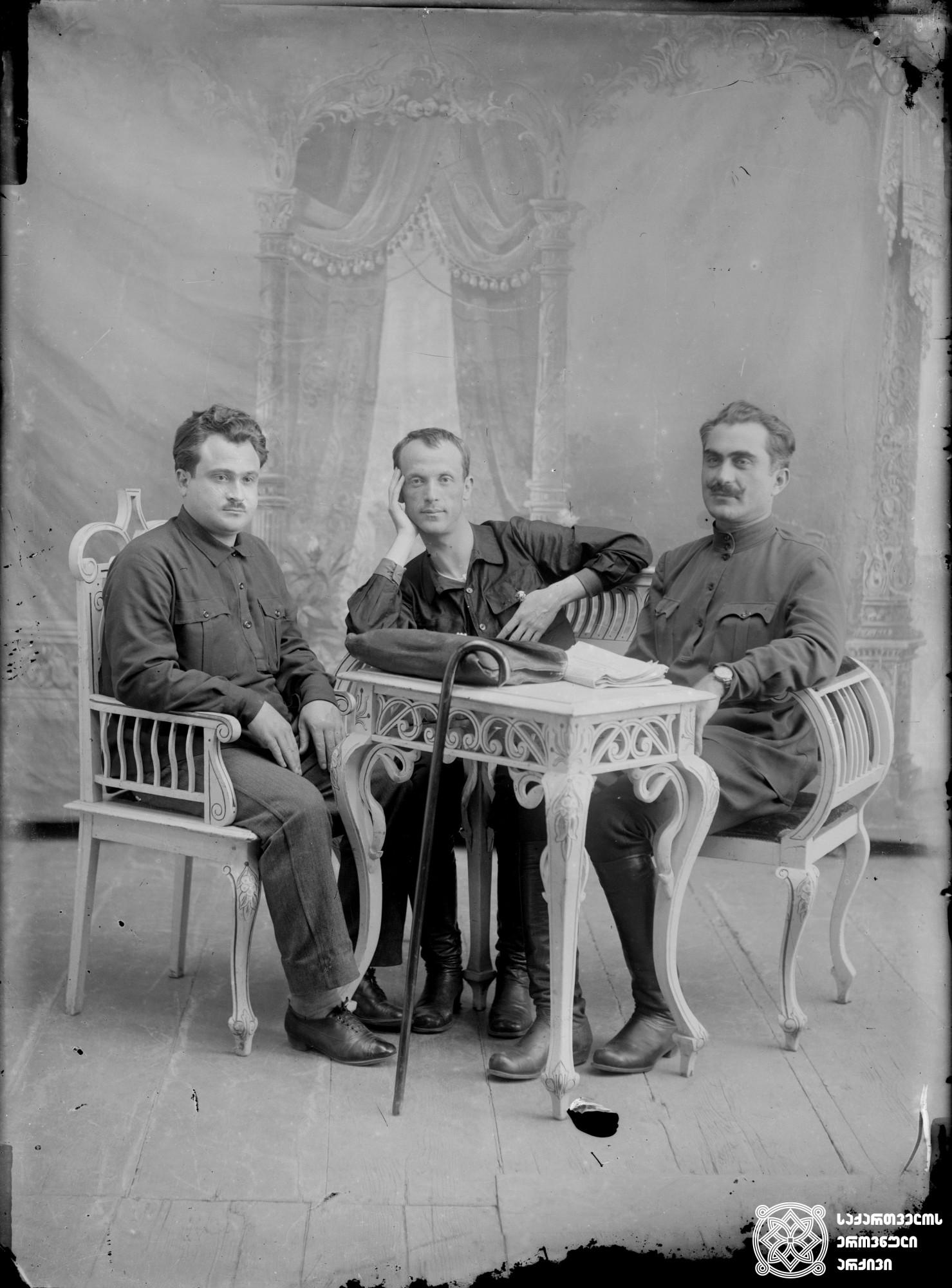 მარცხნიდან: ამბერკი ურუშაძე, უცნობი პიროვნება და დავით ლორთქიფანიძე. <br> მინის ნეგატივი 12X16. <br> From left: Amberki Urushadze, unknown person and Davit Lortkipanidze. <br> Glass negative 12X16.