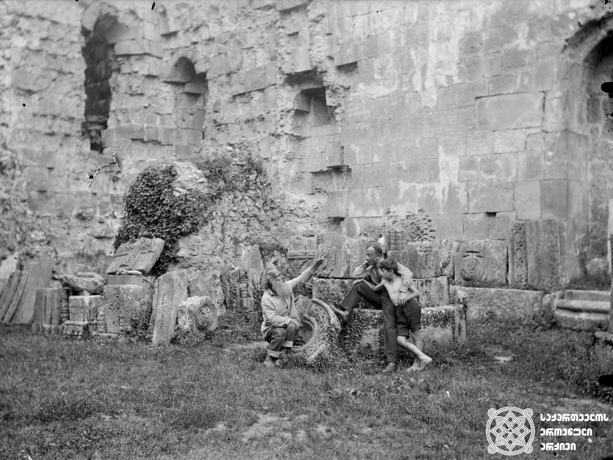 ბაგრატის ტაძრის ნანგრევებთან დავით ჯავრიშვილი ესაუბრება ნანგრევების მცველს, გრიგოლ ბერს. <br> მინის ნეგატივი 13X18. <br> Davit Javrishvili talks to the watchman of the Bagrati temple ruins, monk Grigol. <br> Glass negative 13X18. <br>