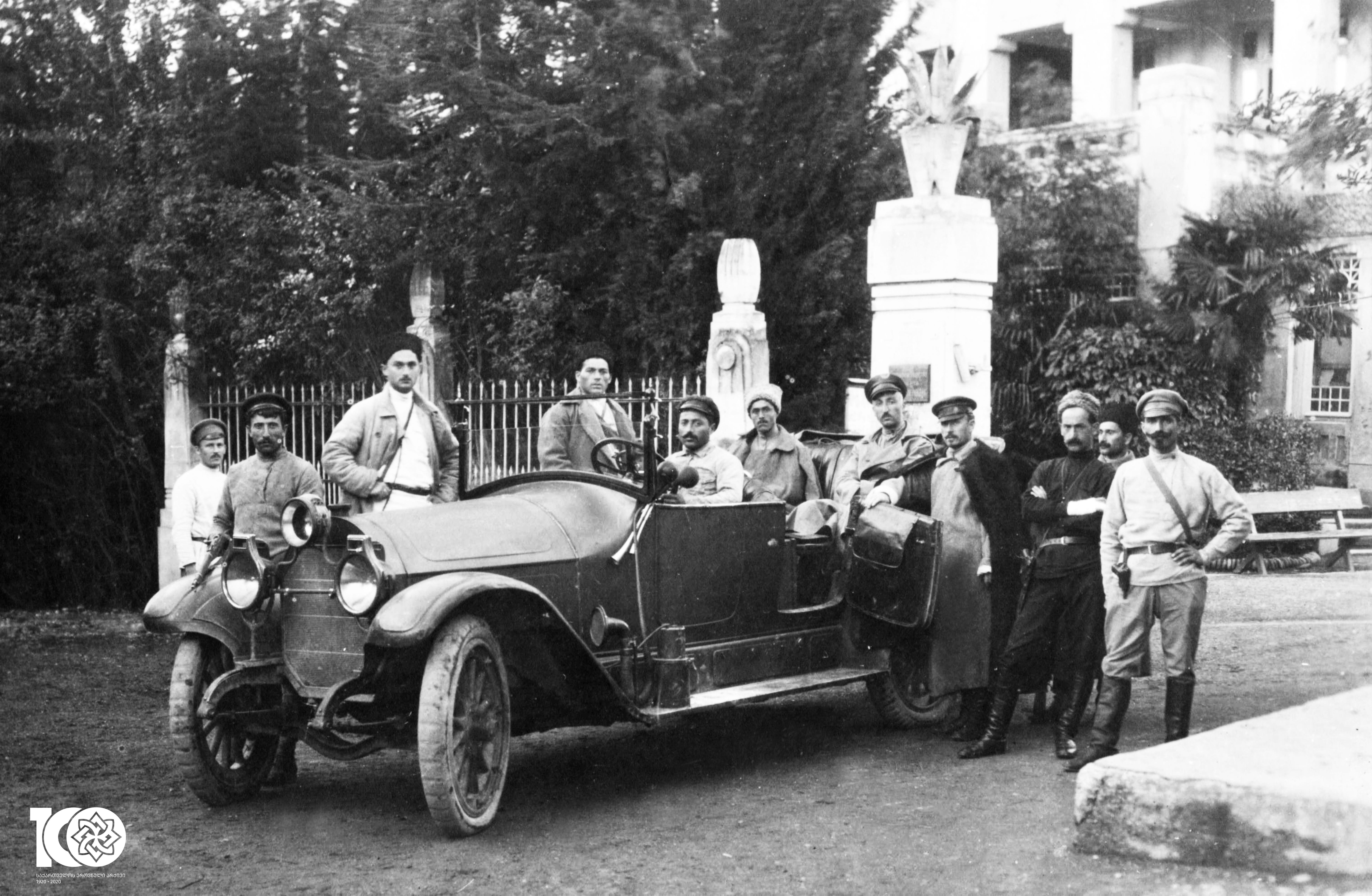 სახალხო გვარდიელები. მანქანის უკანა სავარძელზე ზის ვალიკო ჯუღელი - გვარდიის მთავარი შტაბის უფროსი. ფოტო გადაღებულია გვარდიელების სოჭიდან სოხუმში გამგზავრების წინ. 1918 წელი.  <br> People's Guardsmen. Commander of the guard Valiko Jugheli sits on the back seat. Photo is taken before the departure of the guardsmen from Sochi to Sokhumi. 1918.