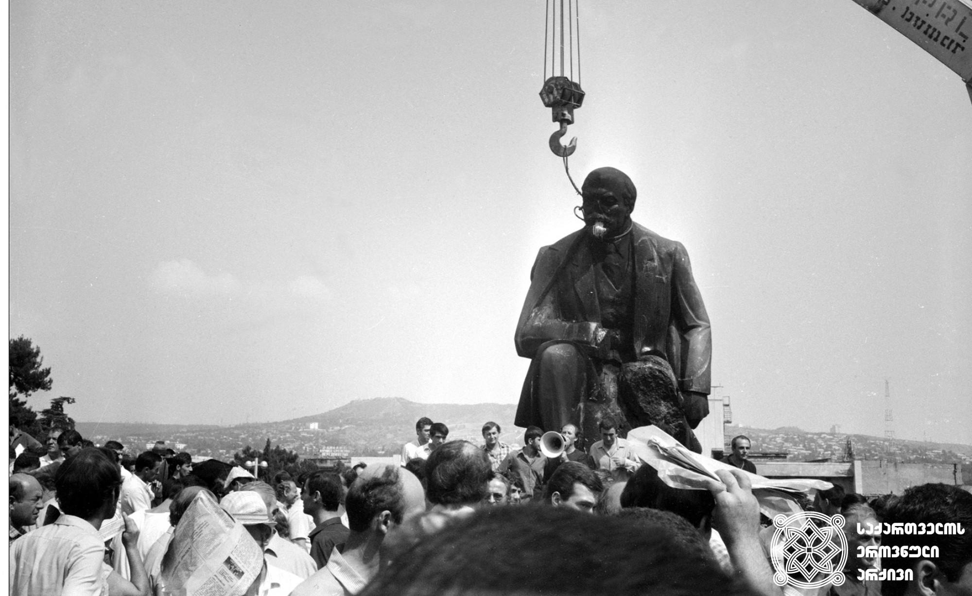 ლენინის ძეგლის დემონტაჟი კომპარტიის ცენტრალური კომიტეტის შენობასთან (დღევანდელი საქართველოს მთავრობის კანცელარიის შენობასთან). თბილისი. <br>საქინფორმის ფოტოქრონიკა. ფოტო: მალხაზ დათიკაშვილი. <br>1990.<br> Dismantling of Lenin Monument in Front of the Building of Central Committee of the Communist Party (Today Building of the Chancellery of the Government of Georgia). Tbilisi. <br> Sakinformi Photography Division. Photo by Malkhaz Datikashvili. <br>1990