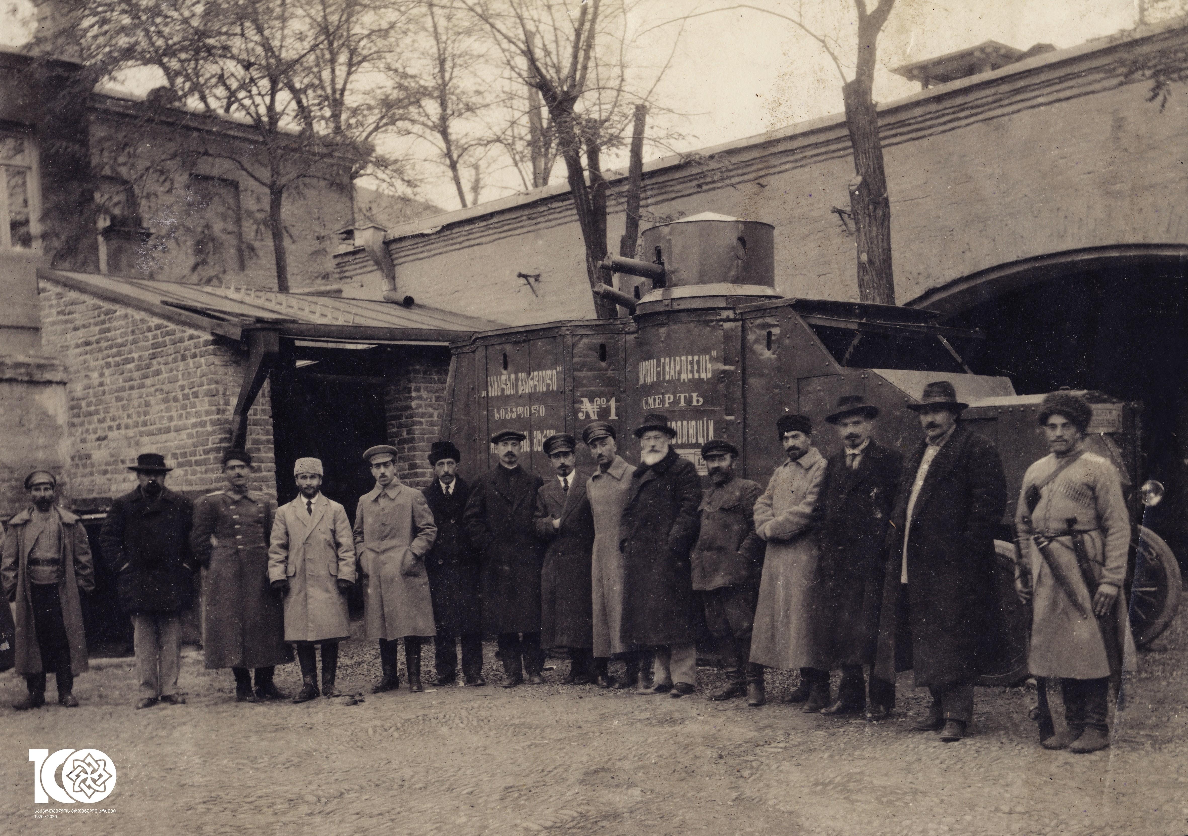 """მთავრობის მეთაური ნოე ჟორდანიას და სახალხო გვარდიის  მეთაური ვალიკო ჯუღელი სახალხო გვარდიის მთავარი შტაბის წევრებთან ერთად ჯავშანმანქანა N1 ,,სახალხო გვარდიელის"""" ფონზე. თბილისი, 1919-1920 წელი <br> The Chairmen of the Geporgian government Noe Zhordania and the head of People's Guard Valiko Jugheli accompanied by a member of the National (People's) Guard in the background of an armoured vehicle. Tbilisi, 1919-1920"""