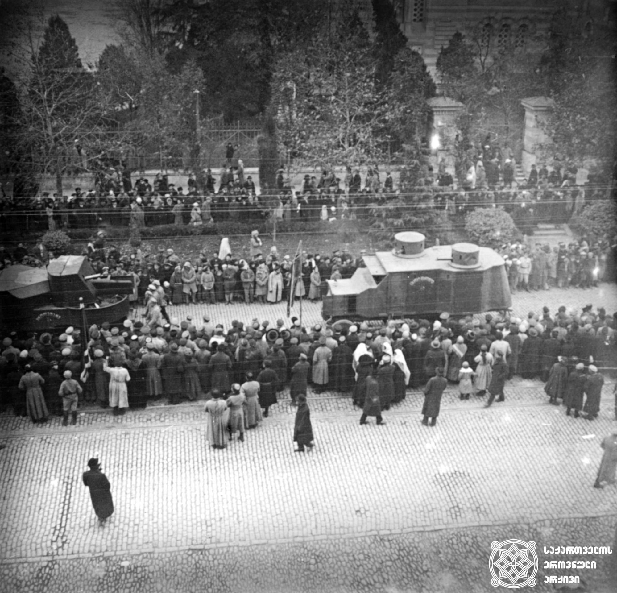 """საქართველოს შეიარაღებული ძალების """"გარფორდისა"""" და """"ოსტინის"""" ფირმის ჯავშანმანქანები რუსთაველის გამზირზე სამხედრო აღლუმზე მსვლელობისას. ჯავშანმანქანები ომში აქტიურ მონაწილეობას იღებდა.  <br> 1920 წელი. <br>  Georgian armed force's - Garford and Austin branded armored cars on military parade on Rustaveli avenue. Armored vehicles took an active part in the war.  <br> 1920."""