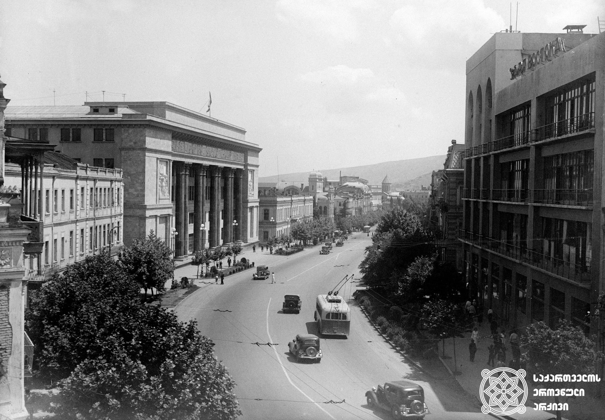 """რუსთაველის გამზირის ხედი. მარქსიზმ-ლენინიზმის ინსტიტუტი მარცხნივ (დღევანდელი სასტუმრო """"ბილტმორი"""") და გაზეთ """"ზარია ვოსტოკას""""რედაქციის შენობა მარჯვნივ (დღევანდელი სავაჭრო ცენტრი """"მერანი""""). თბილისი. <br>ფოტო: ვ. ჩერკასოვი. <br>1938. <br> View of Rustaveli Avenue. Marksizm-leninizm Institute (Today Hotel """"Biltmore"""") on the Left and Newspaper """"Zaria Vostoka"""" Editorial Office (Today Trading Center """"Merani"""") on the Right. Tbilisi. <br>Photo by V. Cherkasov. <br>1938."""