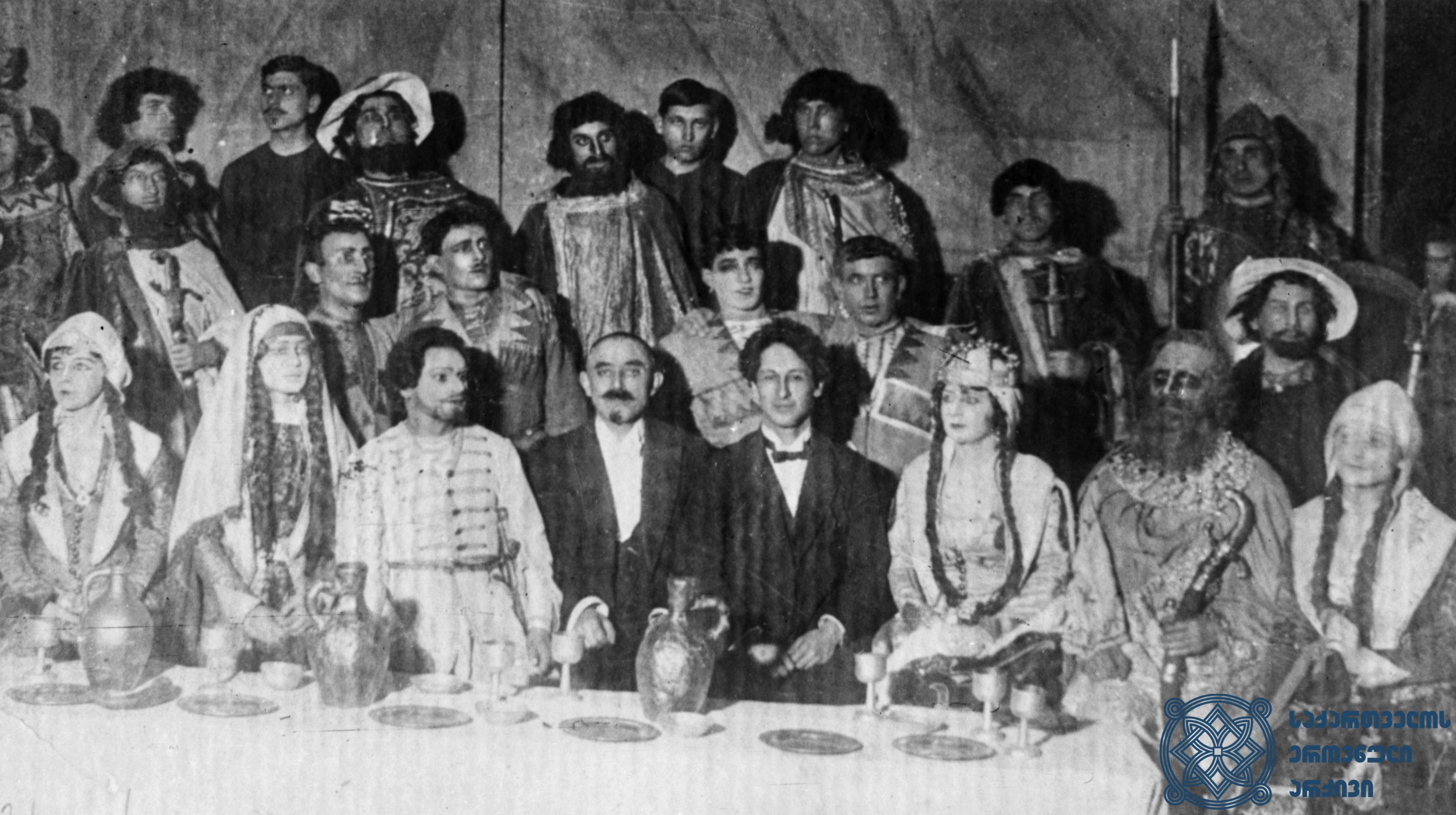 """ზაქარია ფალიაშვილის ოპერა """"აბესალომ და ეთერის"""" პრემიერის შემდეგ გადაღებული ჯგუფური სურათი.<br> ცენტრში, ოპერის მსახიობთა შორის, სხედან: ზაქარია ფალიაშვილი და ალექსანდრე წუწუნავა.<br> 1919 წელი.<br> Group photo taken after the premiere of the opera """"Abesalom and Eteri"""" by Zakaria Phaliashvili Zakaria Phaliashvili and Alexandre Tsutsunava are sitting (in the center) among the opera artists. <br> 1919."""