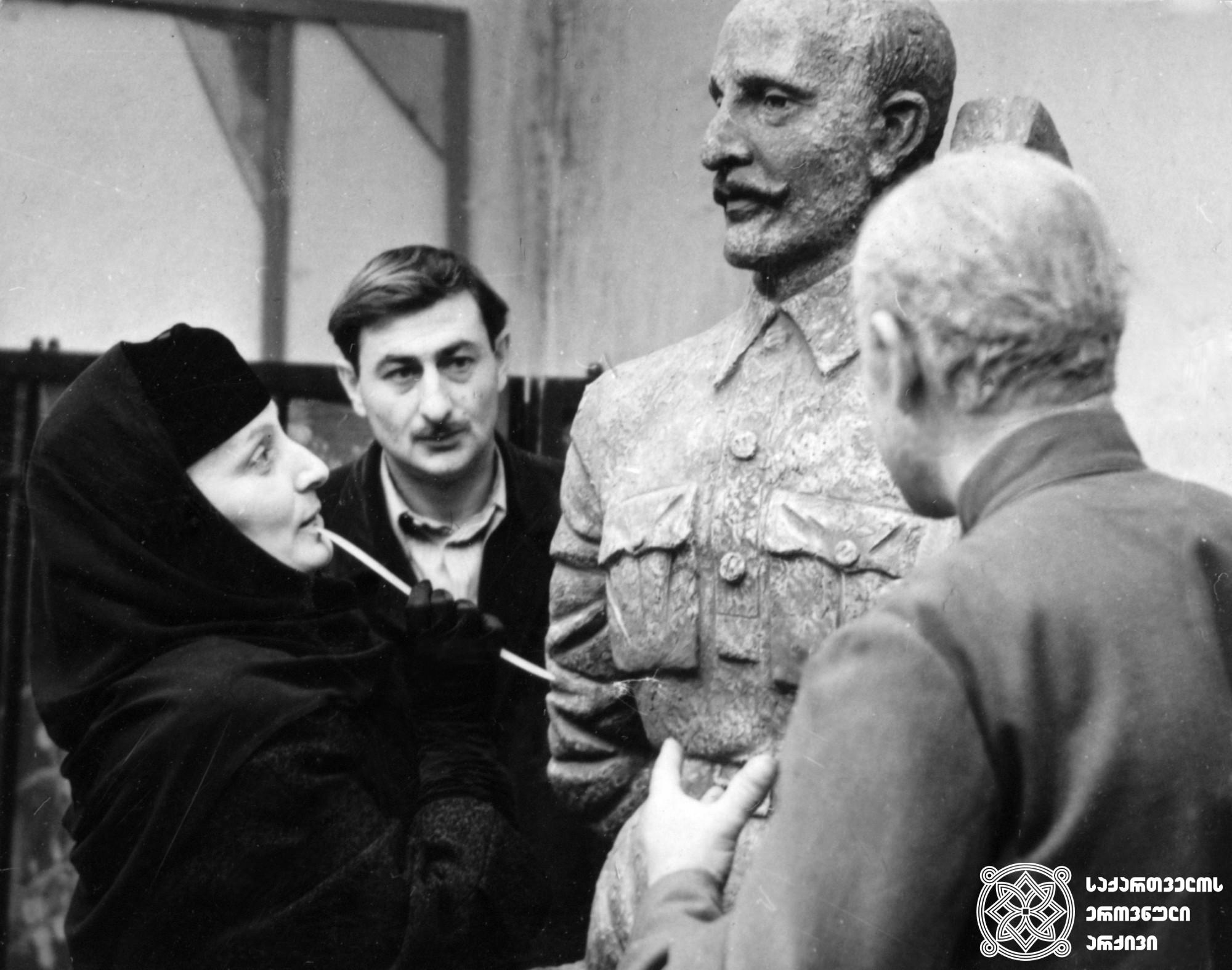 """მხატვრული ფილმი """"არაჩვეულებრივი გამოფენა"""", მსახიობი გურამ ლორთქიფანიძე, სალომე ყანჩელი და ვასილ ჩხაიძე გადასაღებ მოედანზე. <br> რეჟისორი: ელდარ შენგელაია. <br> 1968.   Feature film """"Un Unusual Exhibition"""", Guram Lortkiphanidze, Salome Kancheli and Vasil Chkhaidze on the filming location. <br> Director: Eldar Shengelaia. <br> 1968."""