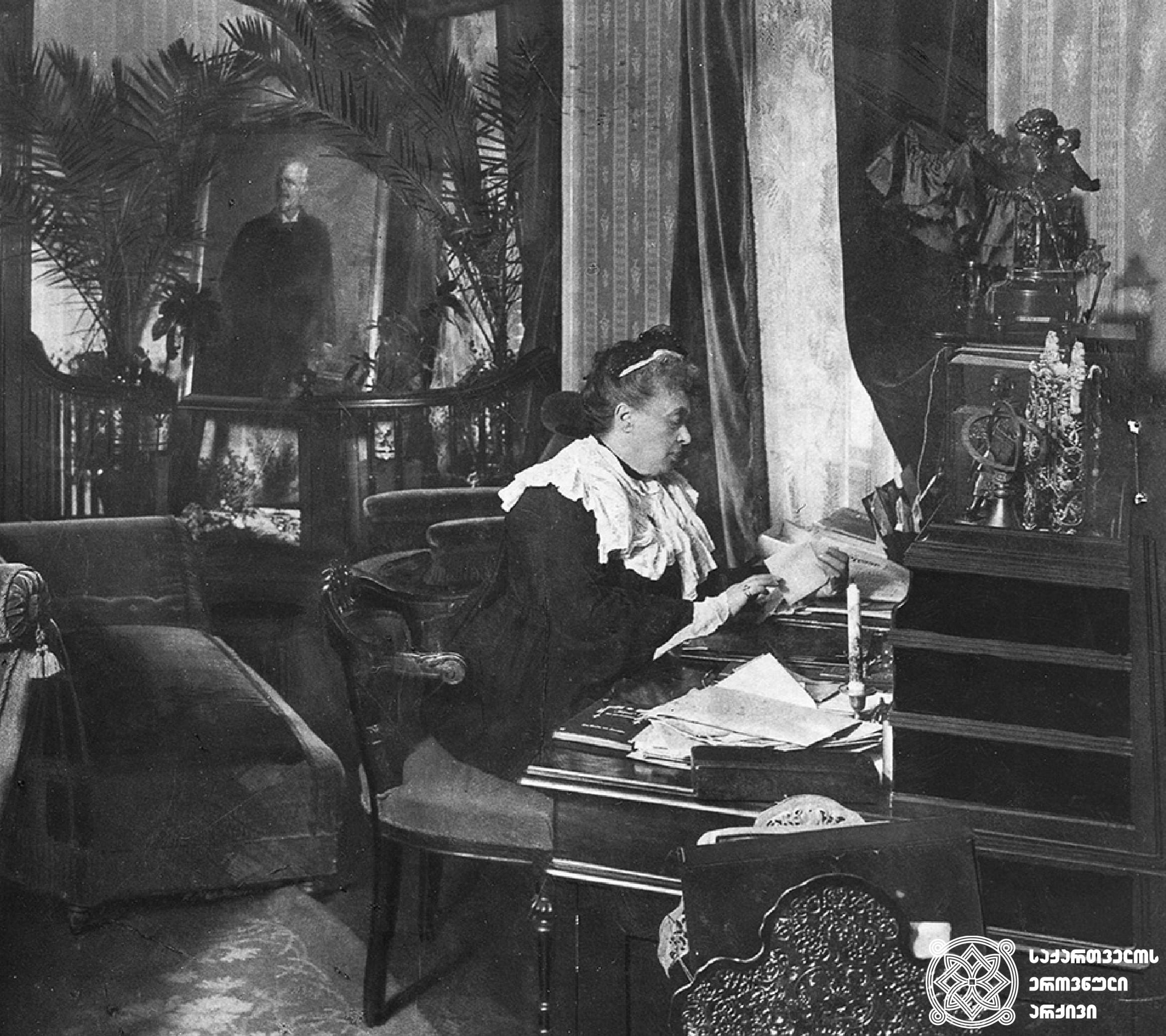 ბერტა ფონ ზუტნერი საკუთარ კაბინეტში, ვენაში. უკანა ფონზე მოჩანს არტურ ზუტნერის პორტრეტი. იგი 1902 წელს გარდაიცვალა. პორტრეტი პალმის რტოებით არის შემკული. <br> გეორგ ჰამანის კოლექციიდან<br> Bertha von Suttner in her study in Vienna. In the background a painting of Arthur, who died in 1902. Portrait is decorated with palm fronds.<br> From the collection of Georg Hamann