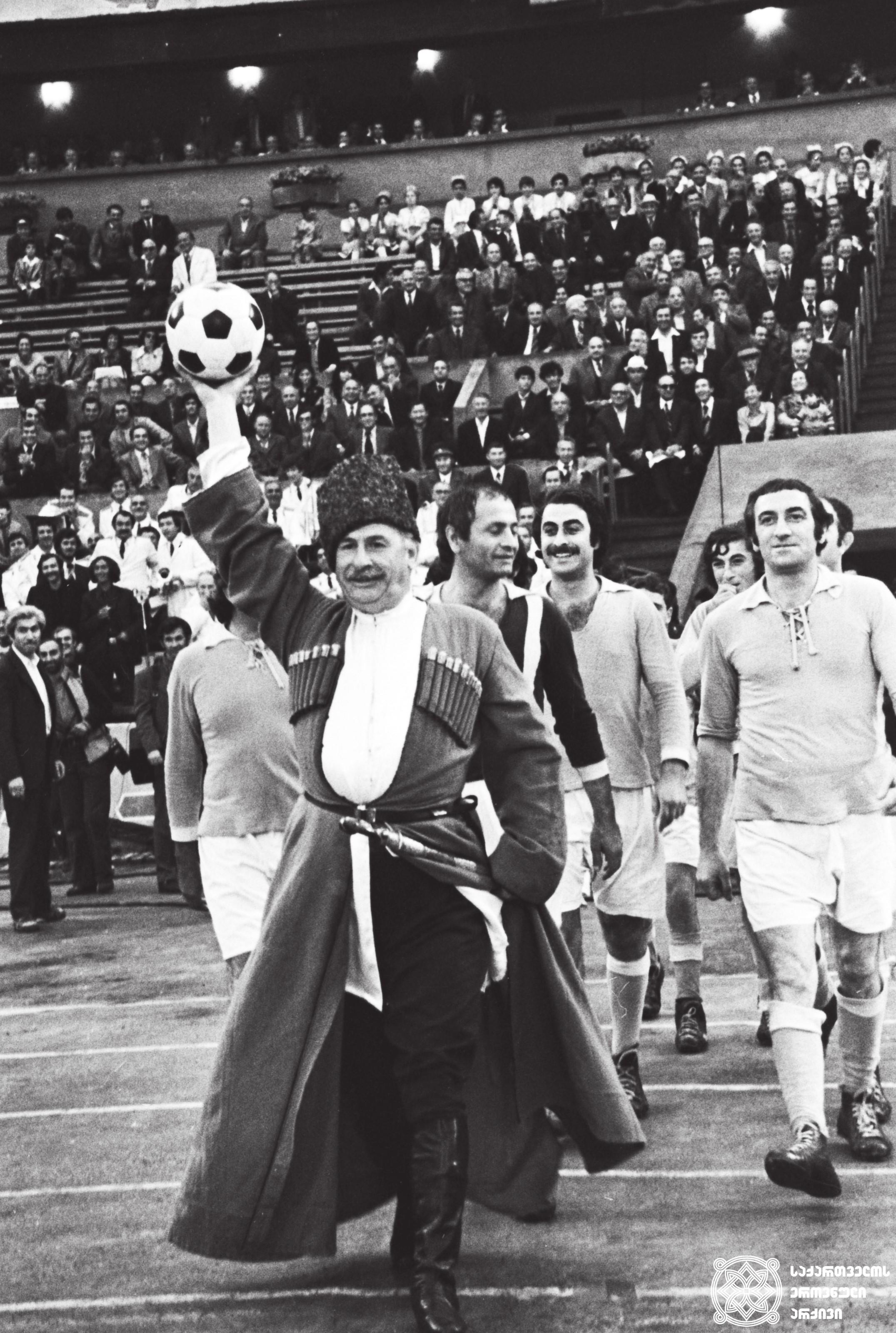 """შეხვედრა მხატვრული ფილმის """"პირველი მერცხალი"""" გადამღებ ჯგუფთან თბილისის სპორტის სასახლეში. მთავარ როლში: დოდო აბაშიძე (ფოტოზე ცენტრში). <br> რეჟისორი: ნანა მჭედლიძე. ფილმი გადაღებულია 1975 წელს <br> Meeting with the film crew of the feature film """"First Swallow"""" at Tbilisi Sport Palace.  In main role: Dodo Abashidze (in the center).  <br> Director: Nana Mchedlidze. Film is shot in 1975"""