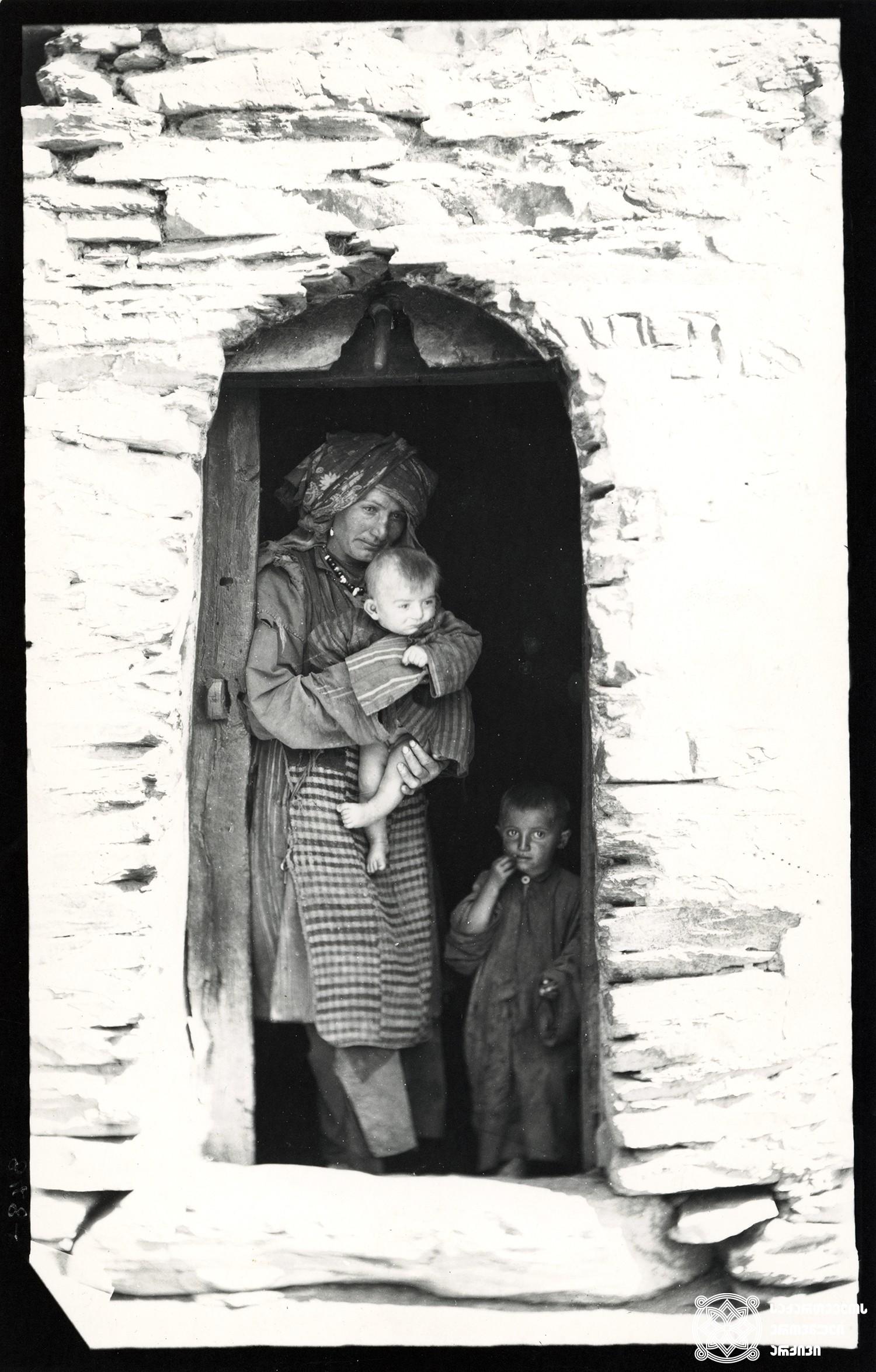 რაჭა, სოფელი ღები. ახალგაზრდა დედა სახლის ზღურბლზე  <br> Racha, village Ghebi. Young mother on the house threshold 1890